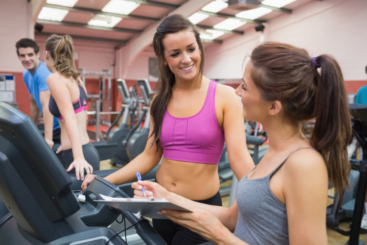 Women smiling in gym while carrying out assessment