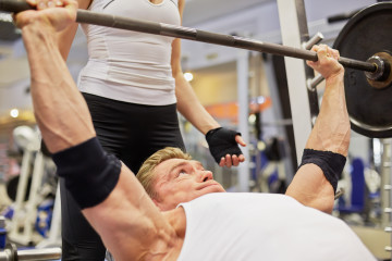 Athlete man does bench press from chest exercise in gym hall